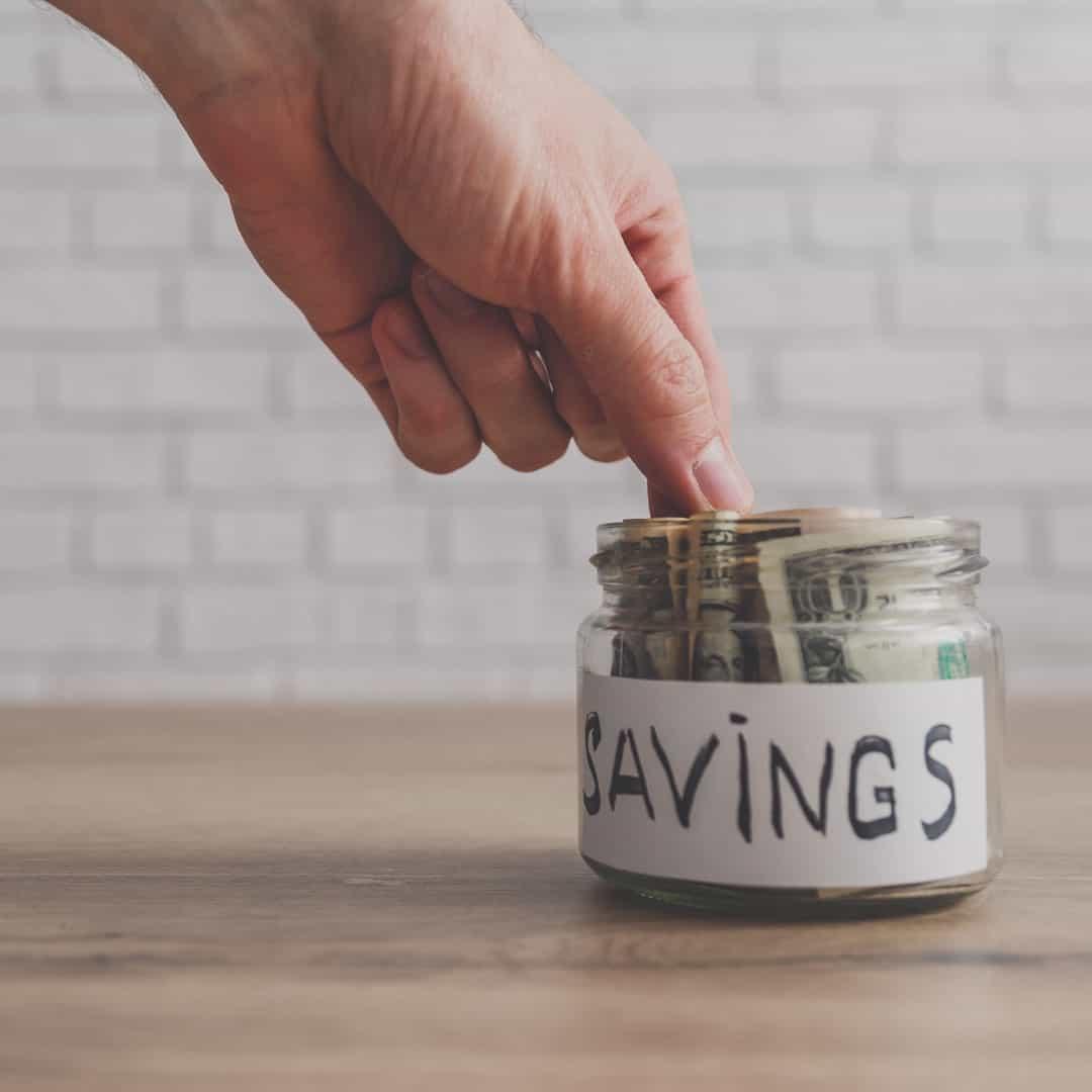 "Hand putting money into a ""savings"" jar."